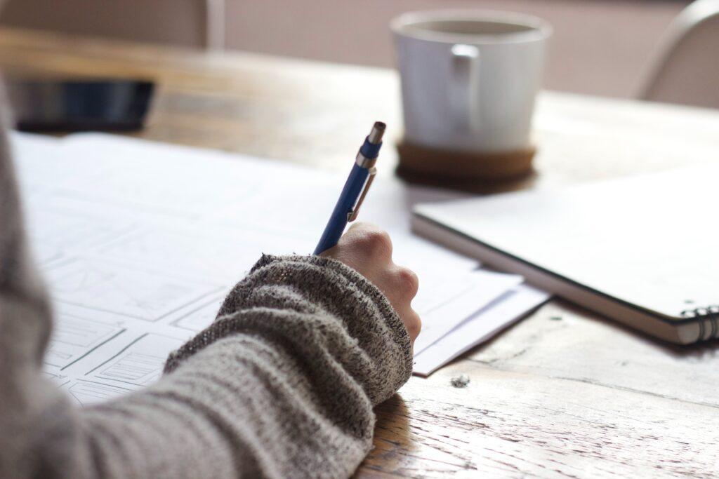 Henkilö kirjoittaa käsin. Oikoluku kielenviilaaja.fi