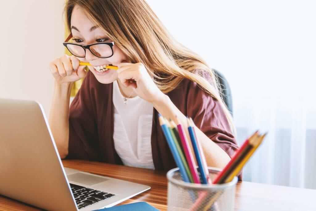 Henkilö katsoo tietokoneen näyttöä ja puree kynää. Opinnäytetyön oikoluku kielenviilaaja.