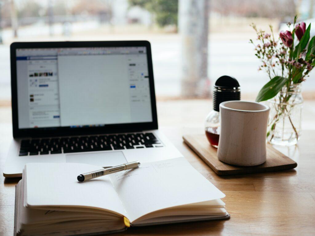 Poydalla avoin tietokone, kirja ja teekuppi. Oikoluku kielenviilaaja.